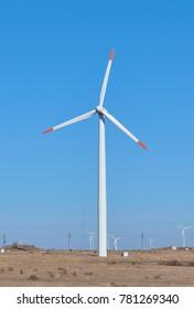 Power saving windmill turbine built on autumn dried field.