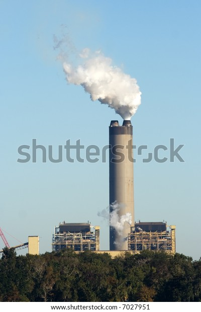power station chimney with white smoke against blue sky