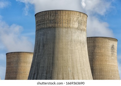 Power station cooling towers emitting steam into a blue sky.