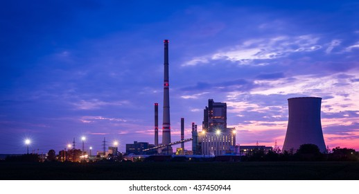 Power station (electric power plant) at sunset. Tall chimney (smoke stack), cooling tower, beautiful, colorful blue, pink and red sky.
