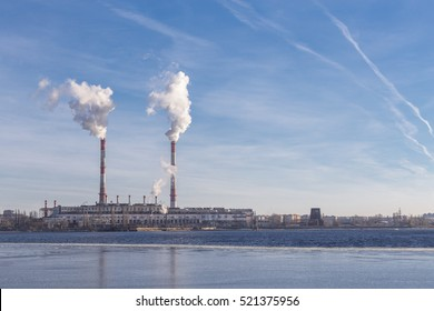 Power station with pipes of which poured smoke on a river. Free copyspace for text. Horizontal image