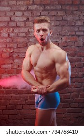 Power, strength, excellent body, bodybuilding, sports concept. Young handsome muscular fit man with perfect body posing on background of brick wall and colorful smoke