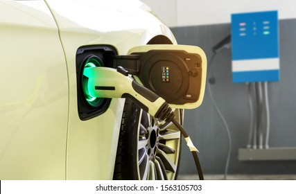 Power supply connect to electric car for add charge to the battery. Charging re technology industry transport which are the future of the Automobile with station charge on background