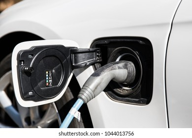 Power supply for electric car charging. Close up of the power supply plugged into an electric car socket. White automobile being charged on bright sunny day.