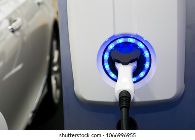 Power supply for electric car charging. Electric car charging station. Close up of the power supply plugged into an electric car being charged