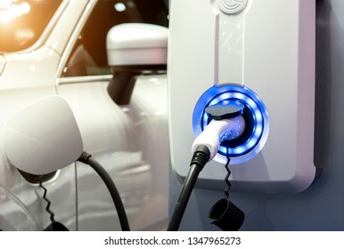 Power supply for electric car charging. Electric car charging station. Close up of the power supply plugged into an electric car being charged.