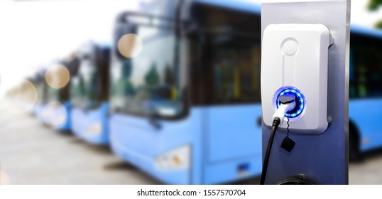 Power supply for electric car charging. Electric car charging station. Close up of the power supply plugged with lot of bus blur background