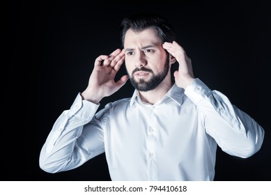 Power of thoughts. Nice serious handsome man holding up his hands and touching his head while concentrating on his thoughts