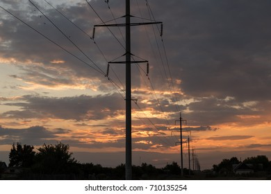 Power transmission line supports leaving the horizon on a sunset background. Concept of electricity.