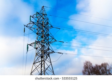 Power transmission line tower against blue sky and clouds with snow-covered high-voltage insulators. Winter time