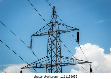 Power transmission tower against blue sky with some low clouds in Kashmir, India