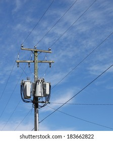 A power utility pole with three transformers lines and insulators against a blue cloud filled sky