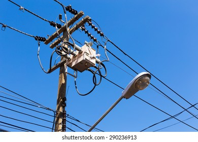 A power utility pole with transformers and street light.