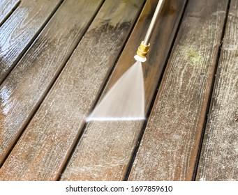 A power washer washing a deck