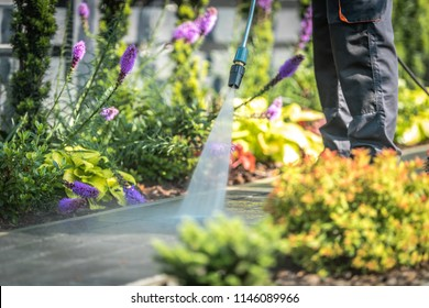 Power Washing Garden Cobble Stone Paths. Outdoor Cleaning Using Pressure Washer. Closeup Photo.