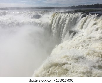 Nature's power as water pours over upper falls at Iguazú Falls, Argentina.