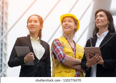 Power of woman. Group portrait of women diversified in career, age and race standing in city looking on the same direction. Two wearing black suits with tablet in hand and another dress like engineer.