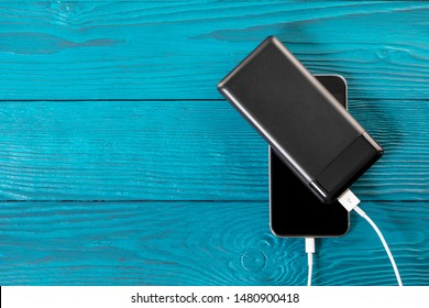 powerbank charges smartphone isolated on wood background