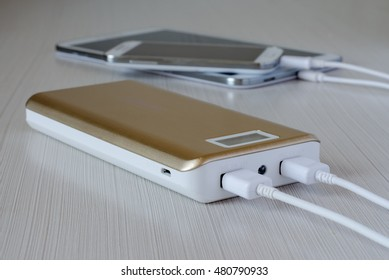 Powerbank charges the smartphone and tablet computer. Close-up