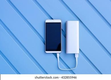 Powerbank charging smartphone - outdoor, blue wooden background