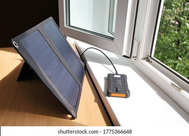 Powerbank on the windowsill is charging from solar energy. Table next to an open window, on it is portable solar charger