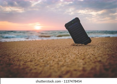 Powerbank in the sand on the background of the rising sun in the cloudy sky and the blue sea. Alternative energy source. battery is charged by solar energy. on desert island. beach