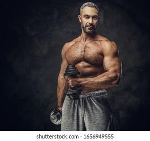 Kräftiger, erwachsener, fit muskulöser Kaukasier-Trainer, der für ein Fotoshooting in einem dunklen Studio unter dem Rampenlicht steht und graue Sportbekleidung trägt, seine Muskeln zeigt und eine Hantel aufstellt, die zuversichtlich aussieht