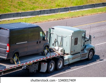 Powerful American big rig popular professional long haul classic semi truck transporting compact commercial cargo mini van fastened on flat bed semi trailer running on wide multiline divided highway