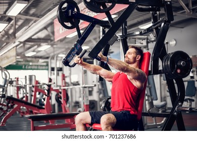 The powerful athlete doing exercises on pectoral muscles in simulator. Gym Machine.
