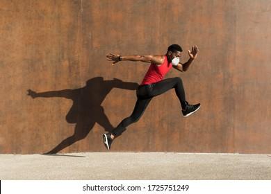 Leistungsstarkes Sporttraining mit n95 Gesichtsmaske zum Schutz vor Covid-19. Der junge schwarze Mann läuft und springt und wirft Schatten auf eine Wand.