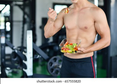 Powerful athletic man with great physique eating a healthy salad.