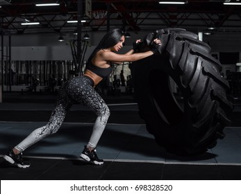 Powerful, attractive muscular girl engaged in crossfit, training with giant tires in the gym. The athlete pushes a large wheel. Exercise with heavy weight in the gym.