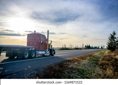 Powerful Big classic American bonnet rig red semi truck with vertical exhaust pipes transporting empty flat bed semi trailer running on the evening road with sunset to warehouse for loading cargo