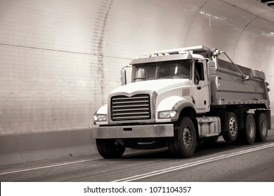 Powerful big rig compact semi truck tipper moves on the road through an underground tunnel with rounded walls