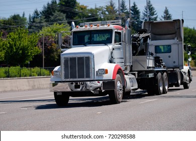 A powerful big rig semi truck tractor tows a broken semi truck on a highway with green trees to the repair and diagnostic site in a specialized repair shop with a qualified mechanics