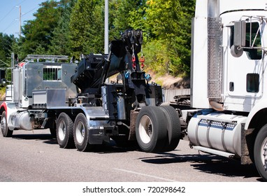 A powerful big rig semi truck tractor tows a broken white semi truck on a highway with green trees to the repair and diagnostic site in a specialized repair shop with a qualified mechanics