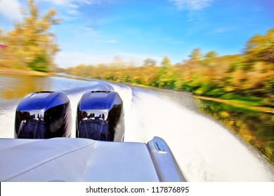 Powerful boat racing at fast speed on the river. Motion blur. View of the stern and two powerful outboard engines.