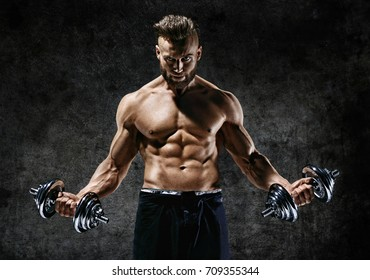 Powerful bodybuilder doing the exercises with dumbbells. Photo of strong male with naked torso on dark background. Strength and motivation.