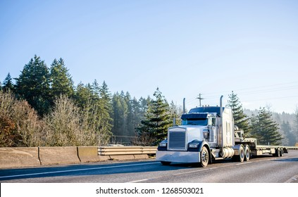 Powerful bonnet American idol black and white big rig long haul semi truck with empty step down semi trailer moving on wide highway with safety fence to warehouse for loading cargo for delivery