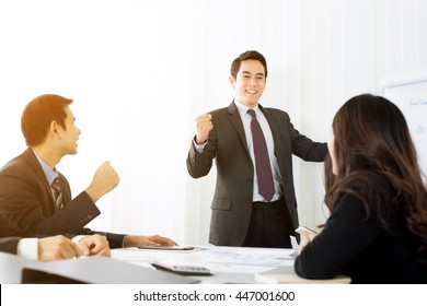 Powerful businessman clenching his fist empowering his colleagues in front of meeting room
