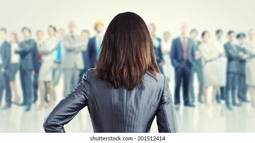 Powerful businesswoman standing with back with business team at background