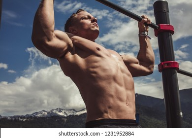 Powerful caucasian bodybuilder with perfect naked upper body with six-pack enjoying adorable mountain landscape during summer workout outdoors, doing chin-ups on horizontal bar.