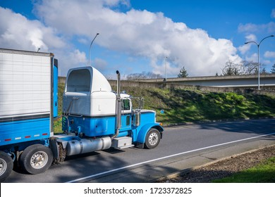 Powerful classic big rig diesel semi truck transporting food cargo in refrigerated semi trailer with refrigerator unit on the front wall running on the highway exit road with overpass intersection