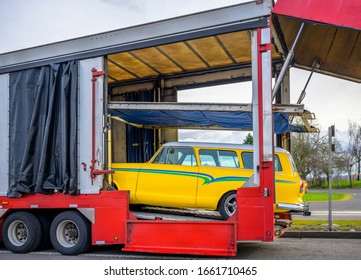Powerful classic open bright red car hauler semi trailer with hoist inside and curtains for safety car transportation standing on the road and unloading yellow retro vehicle