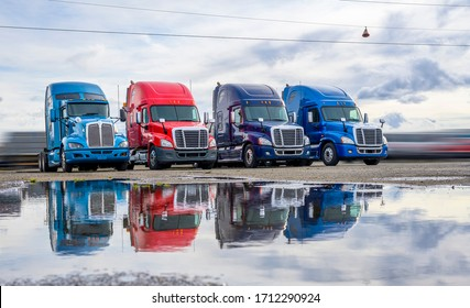 Powerful clean big rigs semi trucks tractors with high cab and rest compartment for truck drivers resting standing on the warehouse parking lot waiting for loaded semi trailer for next delivery