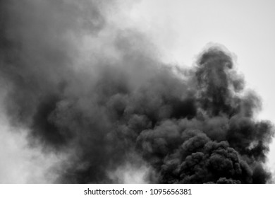 Powerful clouds of black smoke against the sky. Black and white. Background. The problem of waste disposal.