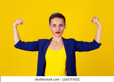 Powerful confident woman flexing her muscles isolated on yellow wall background. Neutral human face expressions, emotions. Beautiful woman in blue suit, yellow shirt with short hair and red lipstick