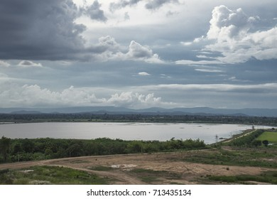 Powerful dark clouds in rainy season over Nong Bua rawe swamp, road, wet land, local agricultural source and village pipe water, Chaiyabhum, water reservoir and dramatic sky. Water management concept.