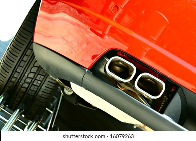 Powerful double exhaust and the left rear wheel of a red sports car in showroom