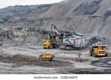 A powerful excavator loads mining trucks. Excavation and loading of rock mass into transport.